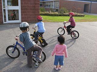 bambini in bicicletta con ruotine a scuola